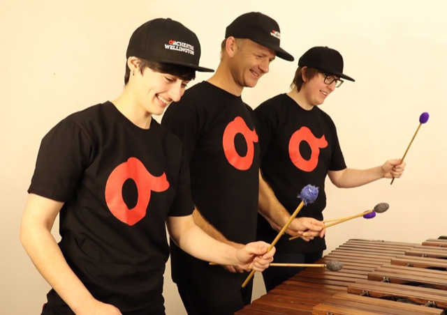 Three musicians, smiling, playing a marimba with 6 wooden mallets