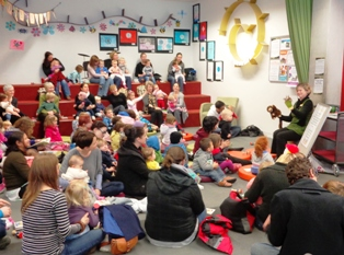 A librarian leads a Baby Rock and Rhyme session in a brightly-decorated library. A large crowd of parents and babies are in attendance, some sitting on the ground, others on the terraces.