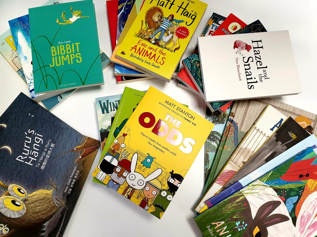 Several piles of brand-new children's books, including picture books, fiction, nonfiction, and comics