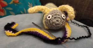 Claude, a grey, green, and yellow caterpillar is sitting on a cushion crocheting the last row of a scarf. The stripes of the scarf are, in order, yellow, white, purple, and the last one is black.