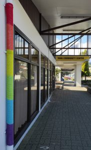 A picture taken looking down the street towards the Tawa Community Centre entrance. It is a sunny day. Lining up with the left side of the picture is a pipe attached to the building, that has is wearing a rainbow cover.