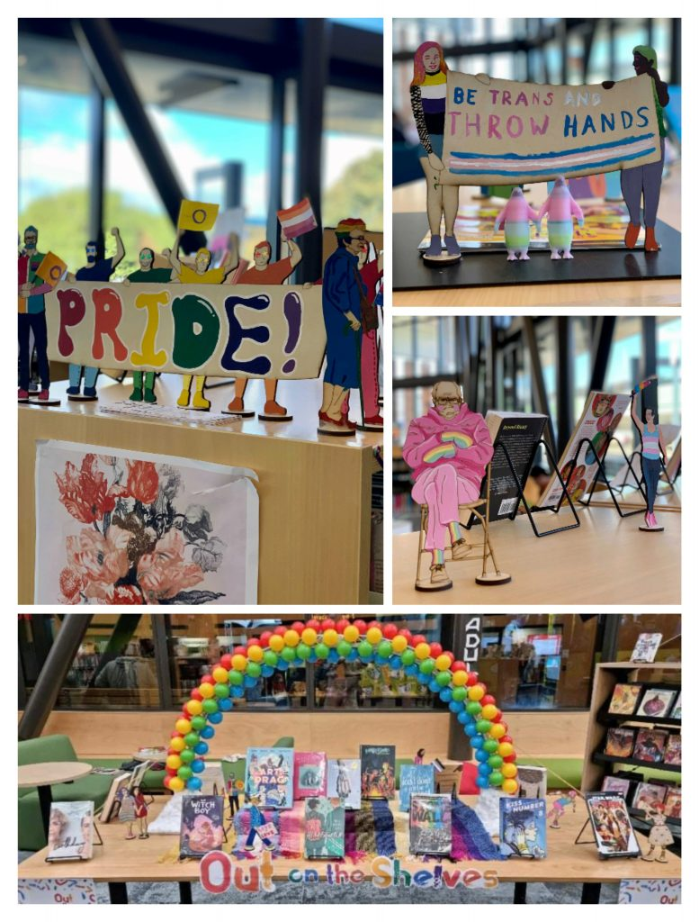 """A collage of four pictures of the Johnsonville library display. Largest at the bottom is the whole display, a table covered with a selection of pride flag scarves, a sign across the from saying """"Out on the Shelves"""", rainbow-themed books on stands, then a large rainbow arch across the whole table. The second picture is a close-up of a group of colourful painted wooden figures holding a sign that says """"Pride!"""". The third picture is of two small wooden people holding a sign that says """"Be Trans and throw hands"""" above two 3D printed penguins that are holding hands. The last picture is of a small wooden Bernie Sanders sitting on a chair in his famous mittens and mask pose. He is wearing all pink, except for his mittens and socks which are rainbow."""