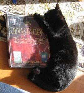 A black cat is lying curled around the right side of a large book. his teeth and front claws are wrapped around the top corner. The title of the book is Devastation: the world's worst natural disasters