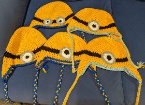 Five crochet beanies, designed to look like Minions