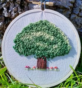 Image shows a hoop embroider, featuring a tree surrounded by small mushrooms on white calico