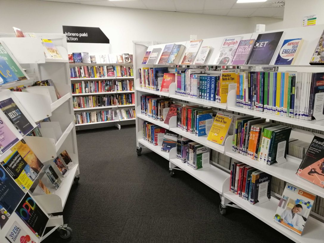Two sets of whaite shelves facing each other, displaying books about learning English.