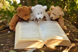 Three teddy bears reading a book in the sun